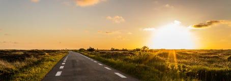 Panoramablick, auf einer Dünenlandschaft im Hinterland mit einer einfachen Straße zum Horizont entlang dem Sonnenuntergang in Dän stockfotos