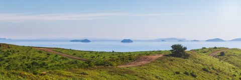 Panoramablick der Landstraße auf die Oberseite von grünen Hügeln lizenzfreies stockfoto