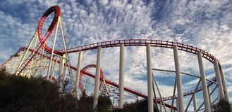Panoramablick der roten Achterbahnbahn mit schönem bewölktem Himmel Lizenzfreie Stockfotografie