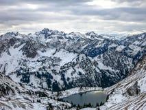 Panoramablick der Schnee-mit einer Kappe bedeckten Alpen und des Gebirgssees Lizenzfreie Stockfotografie