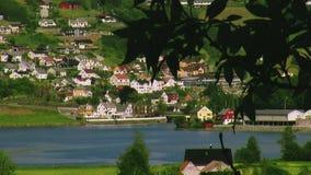 Panoramablick der Stadt an der Küste von Fluss Hügeliges Land Wenig Weißes Haus Wasser Sonniger Tag des Sommers stock footage