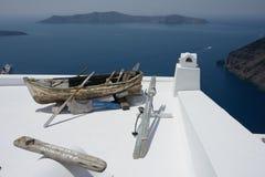 Panoramablick des Meeres um Santorini und des alten hölzernen Bootes auf einer Dachspitze des weißen Gebäudes stockfotografie