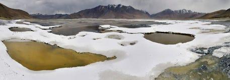 Panoramablick des Salzsees Tsos Kar: weiße Krusten des Steinsalzes nahe dem Ufer des Sees, kleine Pfützen des grünlichen Wassers Stockbild