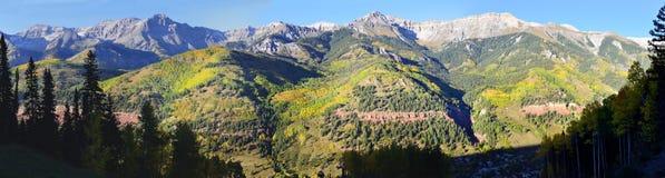 Panoramablick des Schnees bedeckte Berge und gelbe Espe Lizenzfreie Stockfotografie