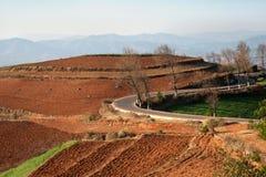 Panoramablick einer Asphaltstraße, die eine rote chinesische Landwirtschaftslandschaft durchläuft Stockbild