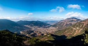Panoramablick eines Dorfs umgeben durch Berge Stockfotos