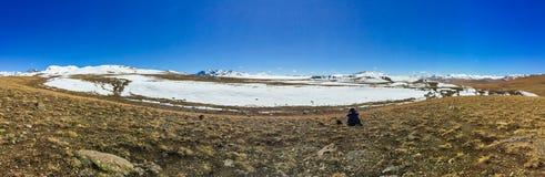 Panoramablick eines Mannes, der allein beim Deosai sitzt, plains Nationalpark, das Land, das durch Schnee bedeckt wird stockbilder