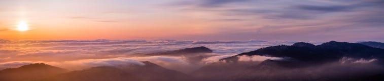 Panoramablick eines Sonnenuntergangs über einem Wolkenmeer, das Süd-San- Francisco Baybereich abdeckt; Gebirgsrücken im Vordergru stockfotografie