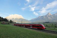 Panoramablick eines Zugs, der auf Grünfelder mit Berg Zugspitze im Hintergrund an einem schönen sonnigen Tag in Lermoos, TIR reis Lizenzfreies Stockfoto