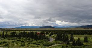 Panoramablick von Bergen unter dunklen Wolken auf dem Horizont und das hochwertige Blockhaus und der Teich und die Brücke im Vord Lizenzfreie Stockfotografie