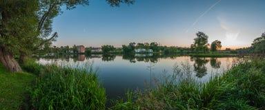 Panoramablick von der Küste durch einen See in einem Stadtpark zu einem Altbau Abendsommerlandschaft Küstenschilfe Klarer Himmel Stockbild