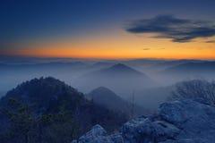 Panoramablick von dunstigen Hügeln während der blauen Stunde und des orange Horizontes in Slowenien lizenzfreie stockfotografie