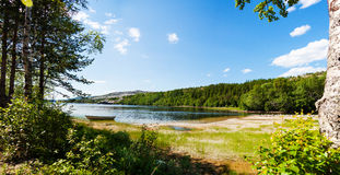 Panoramablick von einem See mit Boot von einem Wald in Nord noch Lizenzfreies Stockfoto
