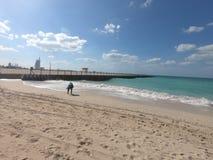 Panoramablick von Jumeirah-Strand und von Burj Al Arab und Ansicht des Piers Frau, die Oberteile am Strand aufhebt lizenzfreie stockfotos