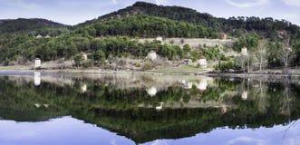 Panoramablick von Steinwindmühlen und von Waldreflexion auf Wasser Stockbilder