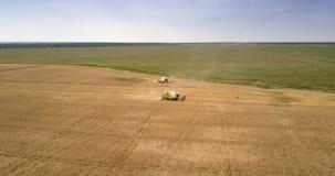 Panoramablicklandwirte auf dem Gebiet und Erntemaschinen schnitten Ernte ab stock video