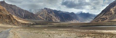 Panoramafoto-Hochgebirgetal: breite braune Hügelschlucht, unter grauem Abendhimmel mit Wolken, Nebel liegt auf Steigungen, Tibet Lizenzfreies Stockfoto