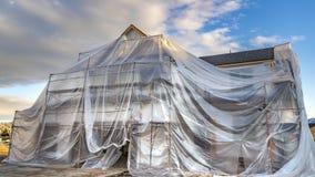 Panoramahuis met plastiek tegen berg en bewolkte hemel in aanbouw wordt behandeld die stock fotografie