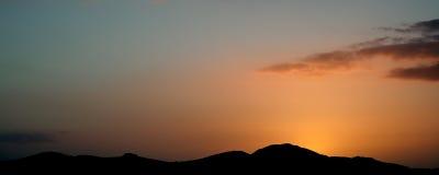 Panoramalandschaftsgebirgsschattenbild gegen vivd Sonnenuntergang Stockbild