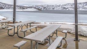 Panoramalijsten en banken binnen een paviljoen die een ijzig meer met sneeuwkust overzien royalty-vrije stock foto's