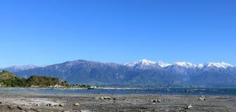 Panoramameer und -schnee bedeckten Berge Kaikoura NZ mit einer Kappe Lizenzfreie Stockfotos