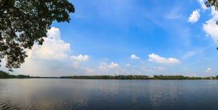 Panoramamening van een rustig meer met een blauwe hemelachtergrond Stock Foto's