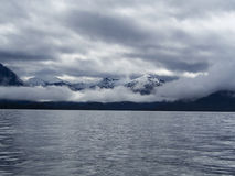 Panoramamening van Sneeuwbergen met Wolken/Mist langs de Kust Royalty-vrije Stock Foto's