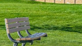 Panoramaramslut upp av en tom bänk mot ett rikt grönt gräs- fält på en solig dag royaltyfria bilder