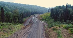 Panoramasatellietbeeld op weg in bossatellietbeeld van kipwagens bij de landweg in bosweergeven van de hommel bij taiga stock videobeelden