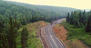 Panoramasatellietbeeld op weg in bossatellietbeeld van kipwagens bij de landweg in bosweergeven van de hommel bij taiga stock video