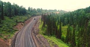 Panoramasatellietbeeld op weg in bossatellietbeeld van kipwagens bij de landweg in bosweergeven van de hommel bij taiga stock footage