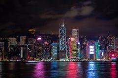 Panoramasikt av den Hong Kong stadsmidtownen på skymning med skyskrapor exponerat reflektera i floden arkivfoto
