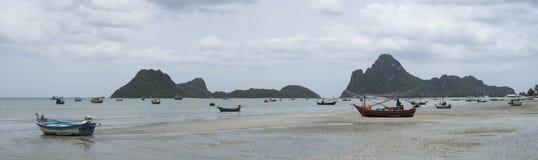 Panoramasikt av den traditionella fiskebåten som lägger på en strand nära havet med det stora och långa berget i bakgrund, molnig Fotografering för Bildbyråer