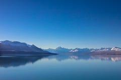 Panoramasikten av snö, berglagret, is och sjön med reflekterar Arkivfoto