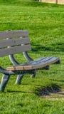 Panoramaslut upp av en tom bänk mot ett rikt grönt gräs- fält på en solig dag royaltyfri bild