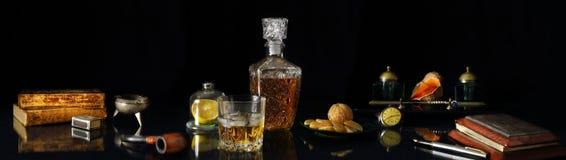 Panoramastilleben med whisky och antikviteten anmärker i retro st royaltyfria foton