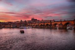 Panoramatic sikt av solnedgången över den Charles bron i Prague royaltyfri fotografi