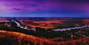 Panoramatic sikt för afton från den Radobyl kullen till floden Labe, guld- fält, kullerevan på horizont och städer Bohusovice nad Royaltyfria Bilder