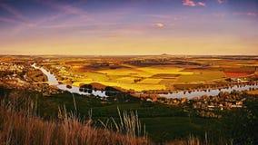 Panoramatic sikt för solnedgång från den Radobyl kullen till floden Labe, guld- fält, kullerevan på horizont och städer Bohusovic Arkivbild