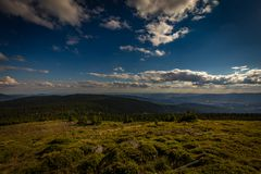 Panoramatic view from peak of Velky Keprnik with pine trees, green grass and dark blue cloudy sky in Jeseniky stock images