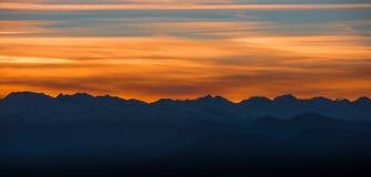 Panoramautsikt av alpina snowcapped bergmaxima på solnedgången Royaltyfri Fotografi