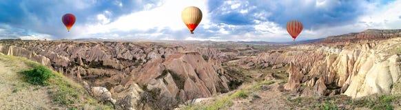 Panoramautsikt av ballongerna för varm luft som flyger för att turnera över berglandskapet Cappadocia royaltyfri fotografi