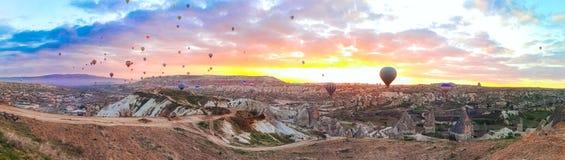 Panoramautsikt av ballongerna för varm luft som flyger för att turnera över sunricen Cappadocia för berglandskapvår arkivfoto