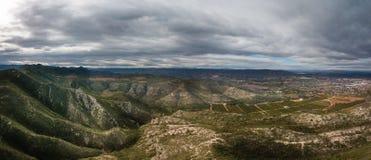 Panoramautsikt av berg med dramatiska himmel- och liten stadkanaler, Spanien i bakgrund arkivbilder