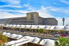Panoramautsikt av byggnad A f?r terminal A, parkeringsoch den partiska sikten av flygtrafikkontrolltornet p? Orlando Internationa royaltyfri fotografi