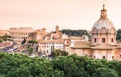Panoramautsikt av Colosseumen och taken på solnedgången, Rome, Italien Arkivbild