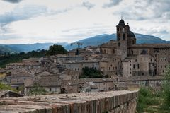 Panoramautsikt av den hertigliga slotten av Urbino i centrala Italien med en dramatisk himmel royaltyfri foto