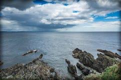 Panoramautsikt av den steniga kustlinjen och dramatisk himmel Arkivfoton
