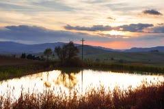 Panoramautsikt av lite dammet, Rolling Hills, himmel och moln på solnedgången i tuscan bygdlandskap, Tuscany, Italien royaltyfri bild