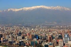 Panoramautsikt av mitten av Santiago de Chile på aftonen med snöig Anderna i bakgrunden Royaltyfri Fotografi